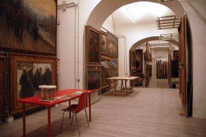 Qui sopra, il deposito quadri di Palazzo reale. In alto, una panoramica della piazza del Plebisciro con la reggia napoletana dove si trova anche la biblioteca nazionale