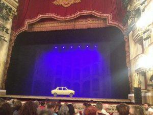 Qui sopra, il taxi giallo sul palco del San Carlo che simula la macchina del tempo. In alto, gli attori in scena alla fine della serata