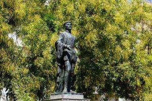 Qui sopra, la statua di Don Giovanni a Siviglia. In alto, una scena dello spettacolo