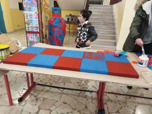 Qui sopra, un momento del laboratorio- In In alto, i pannelli con il corridore. In basso, la scultura e il mosaico realizzati dagli alunni