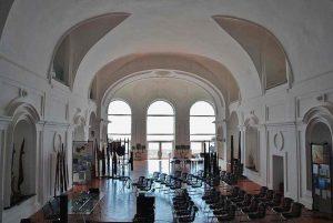 Qui sopra, la fondazione De Felice a Palazzo Donn'Anna. In alto, il complesso Olivetti di Pozzuoli